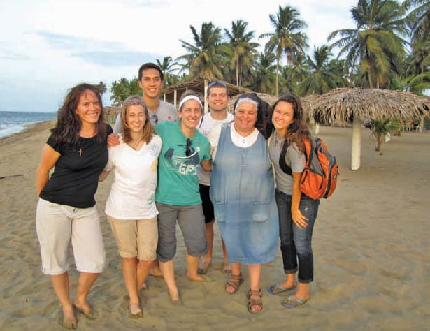 Missionary of the Most Sacred Heart of Jesus (MSC) Sister Lisa Valentini gathers on the beach in the Dominican Republic with college students and adults who joined her for Mission Experience. (Photo courtesy MSCs of Reading)
